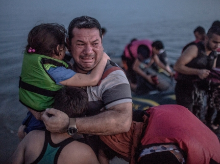 A Syrian refugee holding his son and daughter breaks out in tears of joy after arriving on the shore of the island of Kos in Greece.